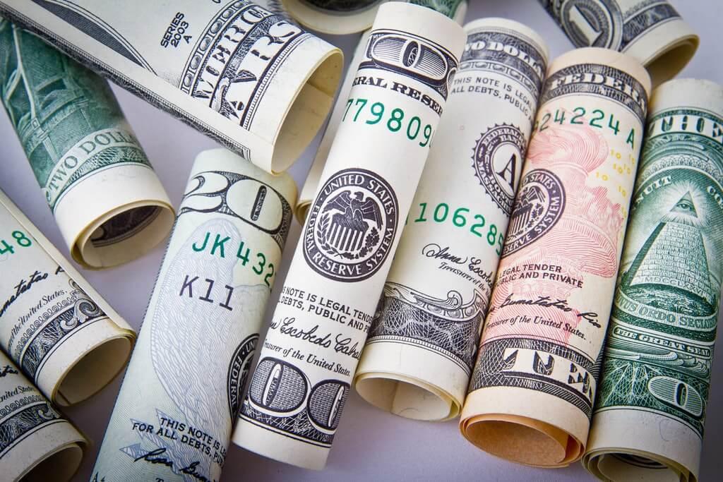На фото изображены деньги, свернутые в трубочку.
