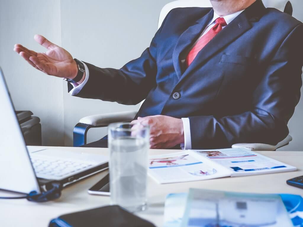 На фото мужчина в пиджаке сидит в офисном кресле.