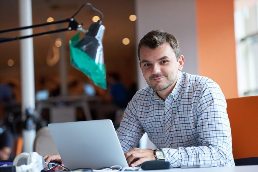 На фото мужчина за рабочим ноутбуком.