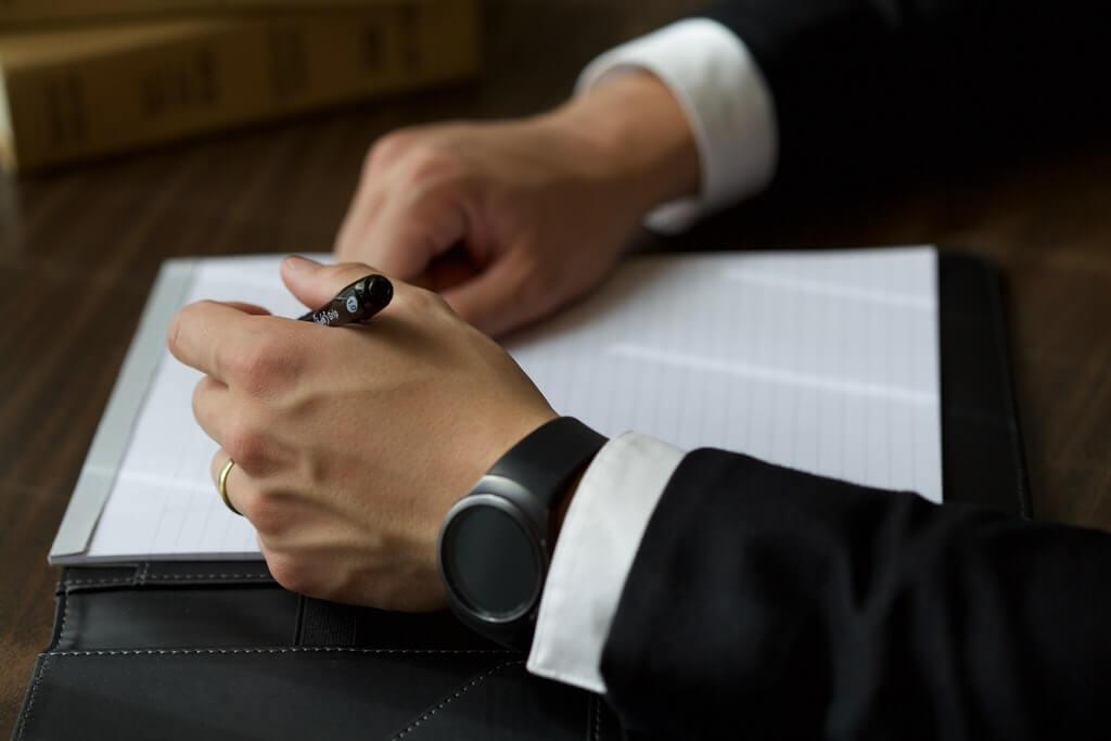 На фото мужчина в костюме подписывает договор