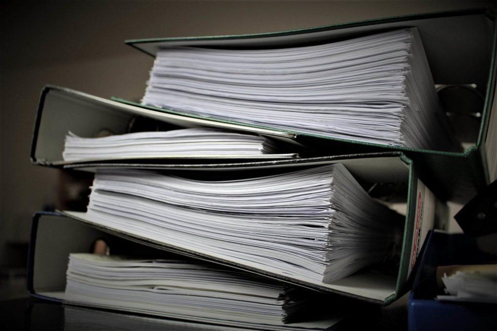 На фото изображены папки с документами.
