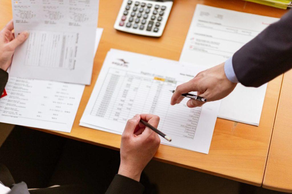 На фото изображен процесс работы с документами в офисе.