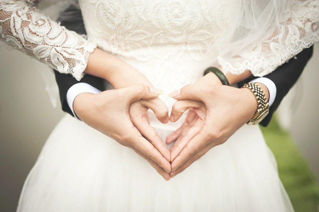 На фото изображен супруг, который обнимает свою жену сзади.