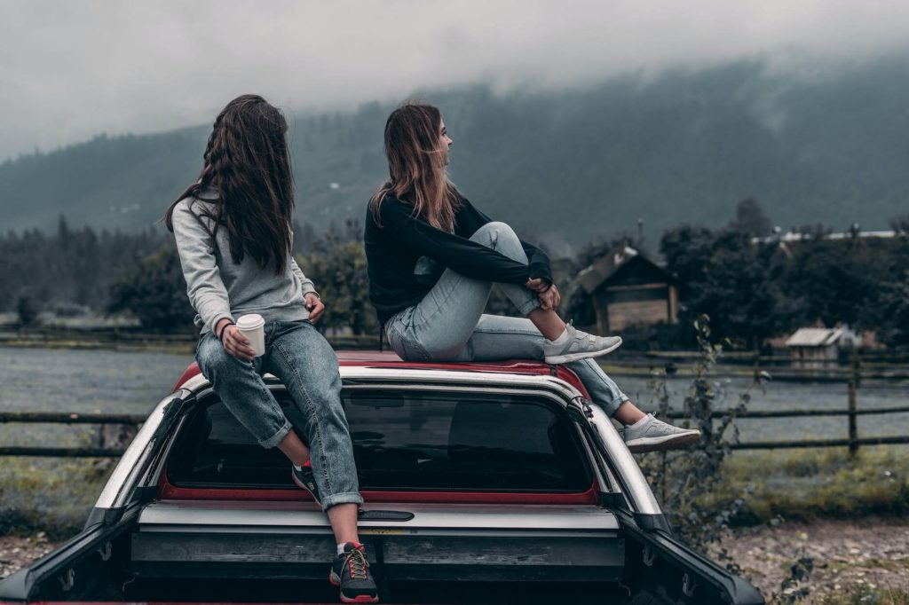 На фото две девушки сидят на кузове авто.