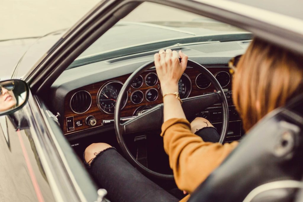 На фото девушка за рулем автомобиля.