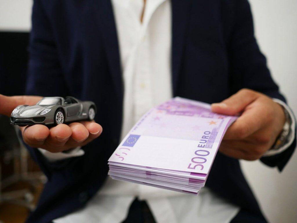 На фото мужчина предлагает машину и деньги.