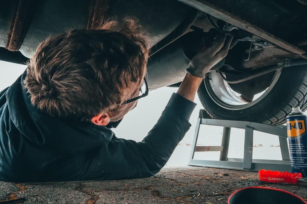 На фото человек занимается ремонтом авто в гараже.