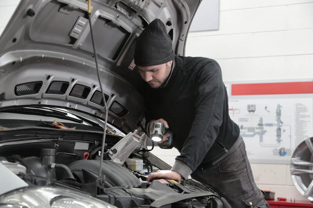 На фото мужчина в гараже чинит авто.
