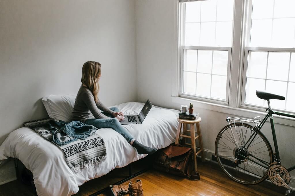 На фото девушка в комнате работает за ноутбуком.