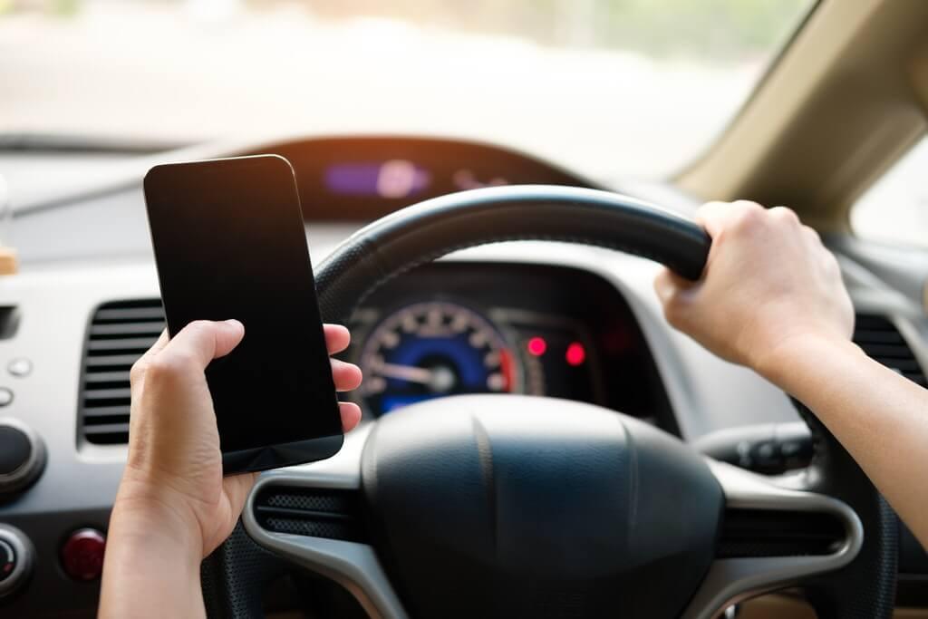На фото водитель держит в руке телефон.