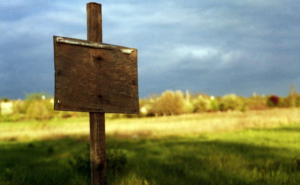 На фото изображен земельный участок с табличкой.