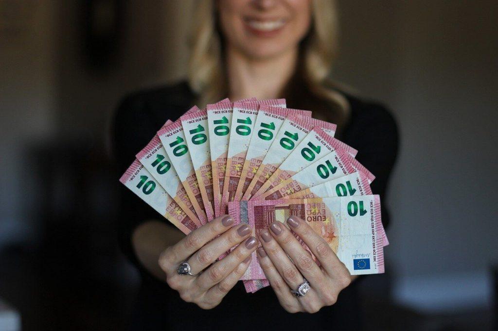 На фото женщина держит в руках деньги веером.