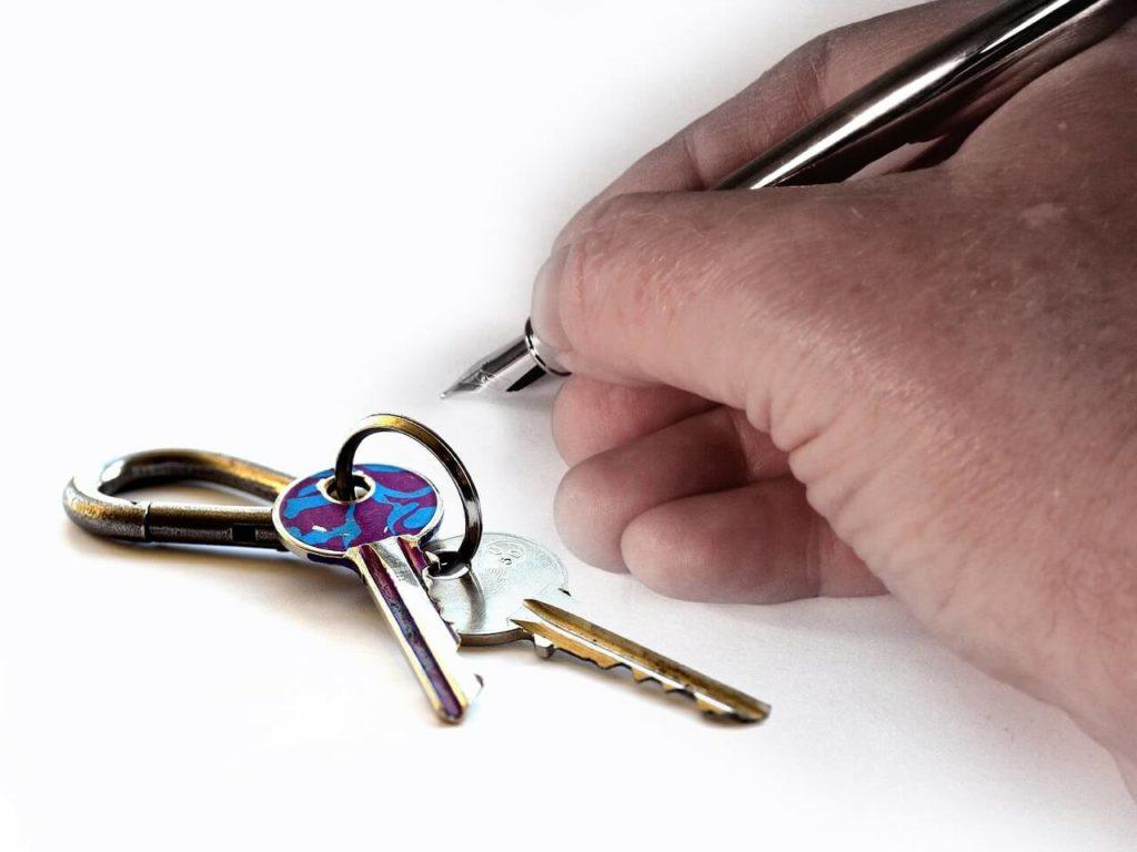 На фото мужчина подписывает договор на котором лежит связка ключей.