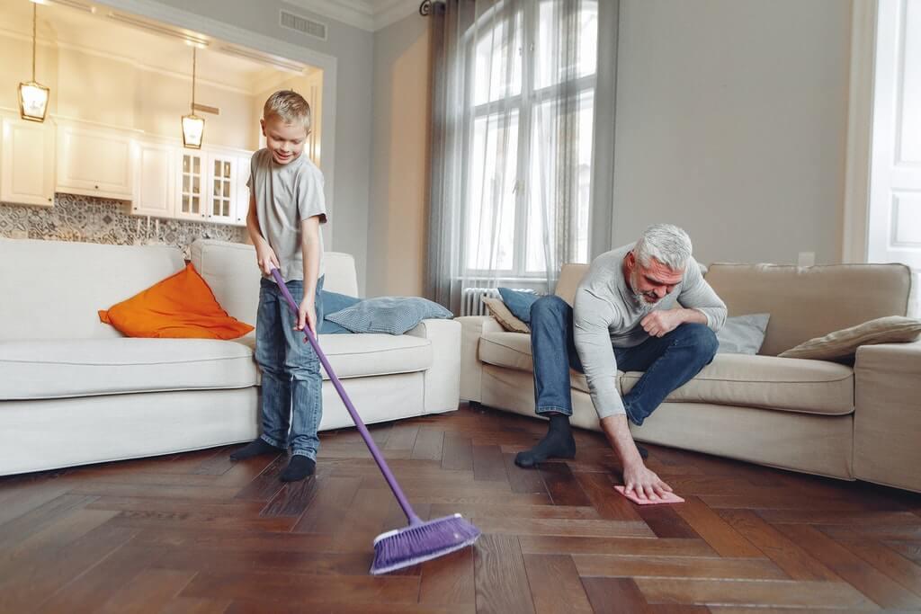 На фото семья занимается уборкой в доме.