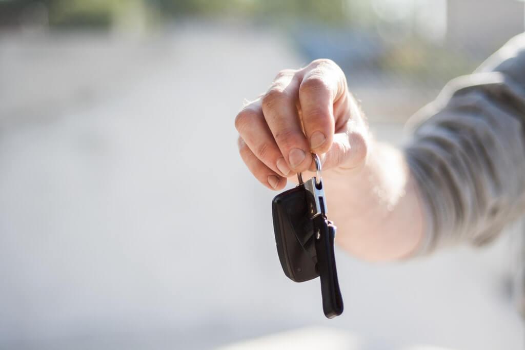 На фото человек держит в руке ключи от авто.