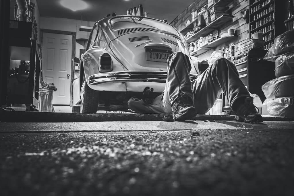 На фото мужчина ремонтирует автомобиль в гараже.