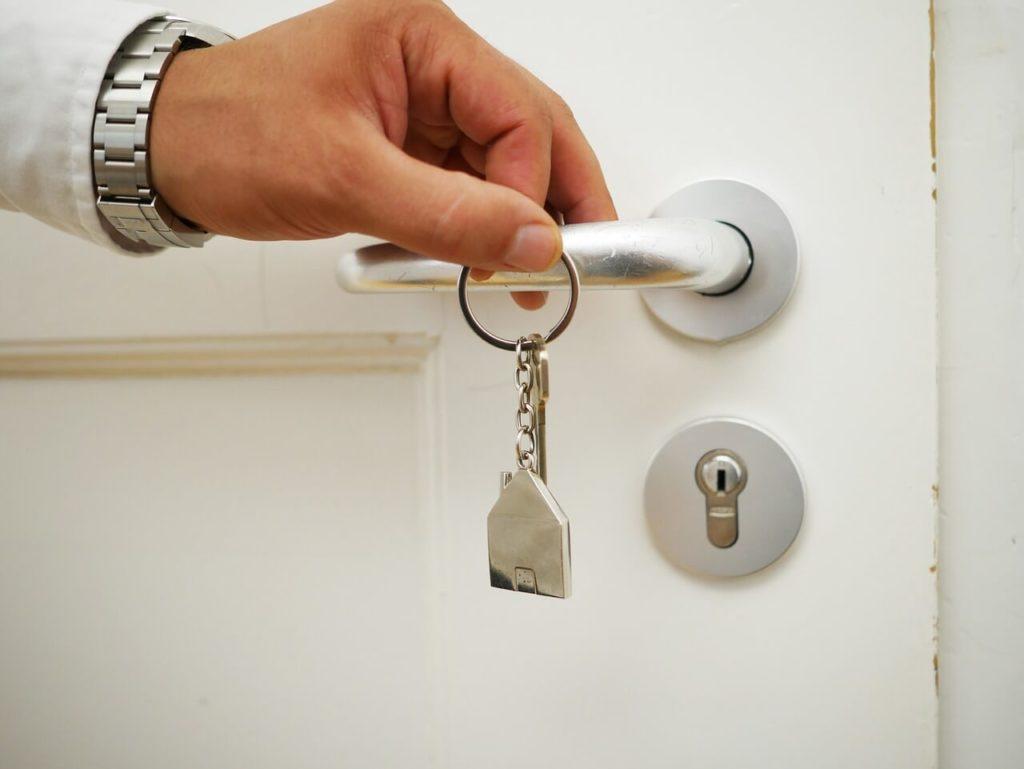 На фото мужчина с ключами открывает дверь.
