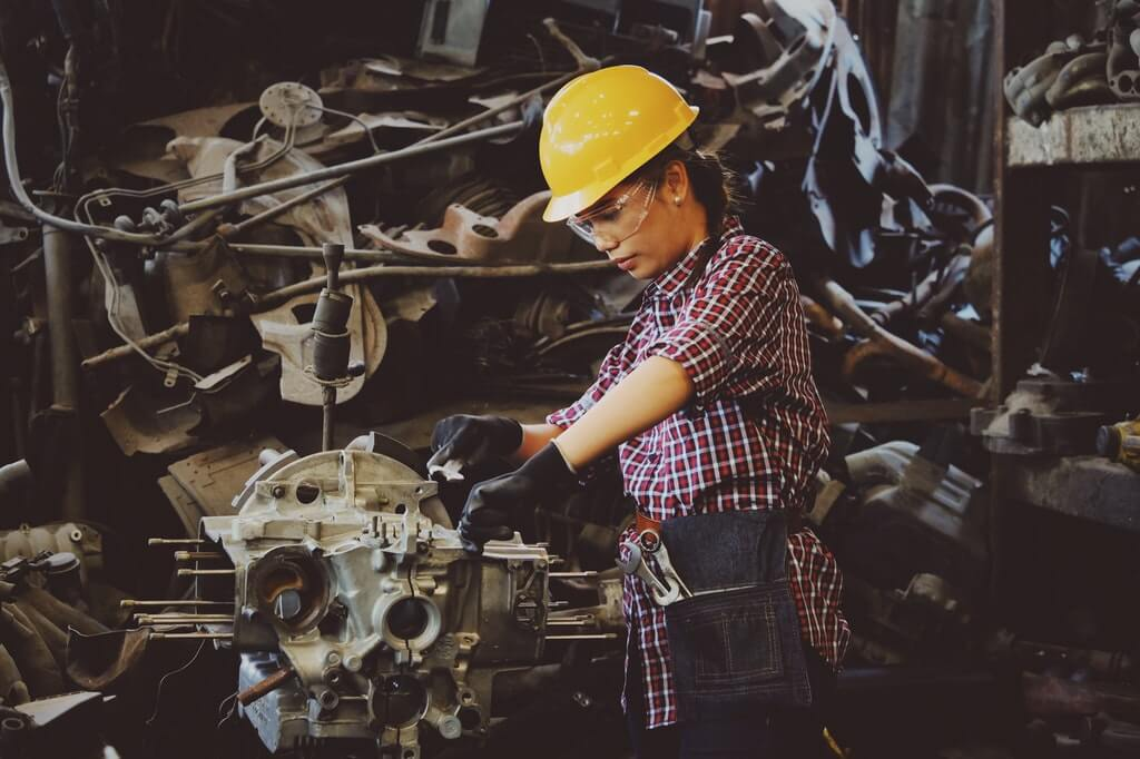 На фото изображена девушка в каске за рабочим процессом.