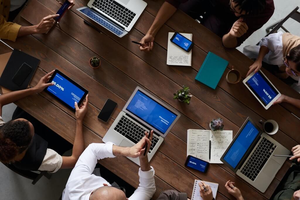 На фото группа людей сидят за одним столом в офисе.