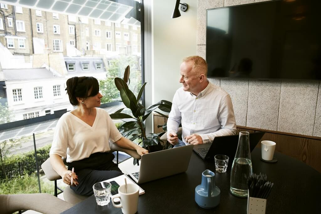 На фото женщина консультирует клиента в офисе.