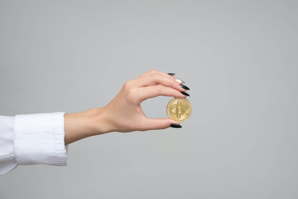 На фото девушка держит в руке монету.