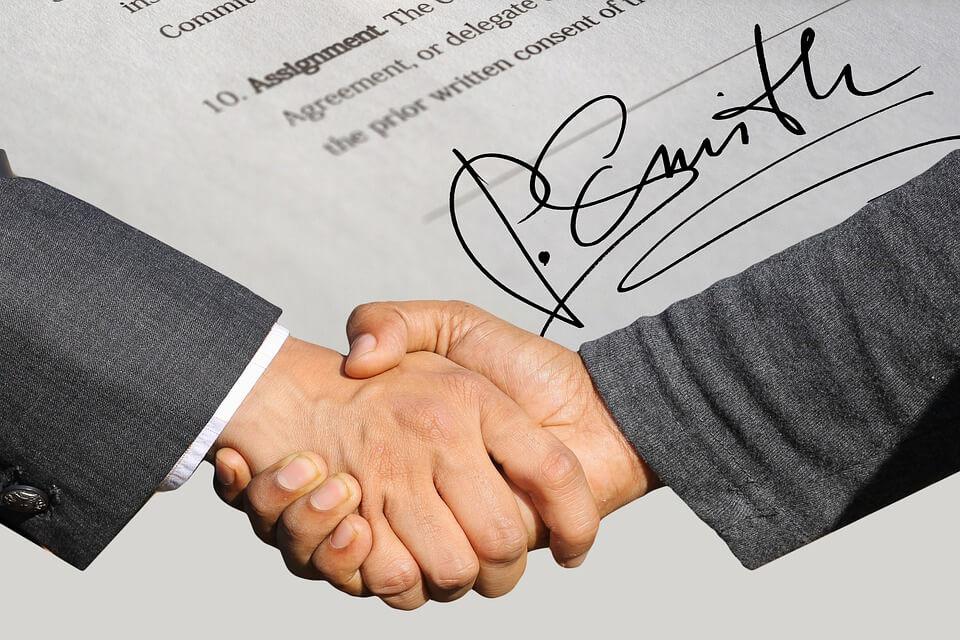 На фото две стороны заключили сделку с рукопожатием.