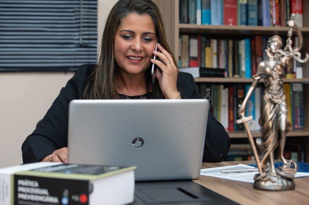 На фото женщина на рабочем месте говорит по телефону.
