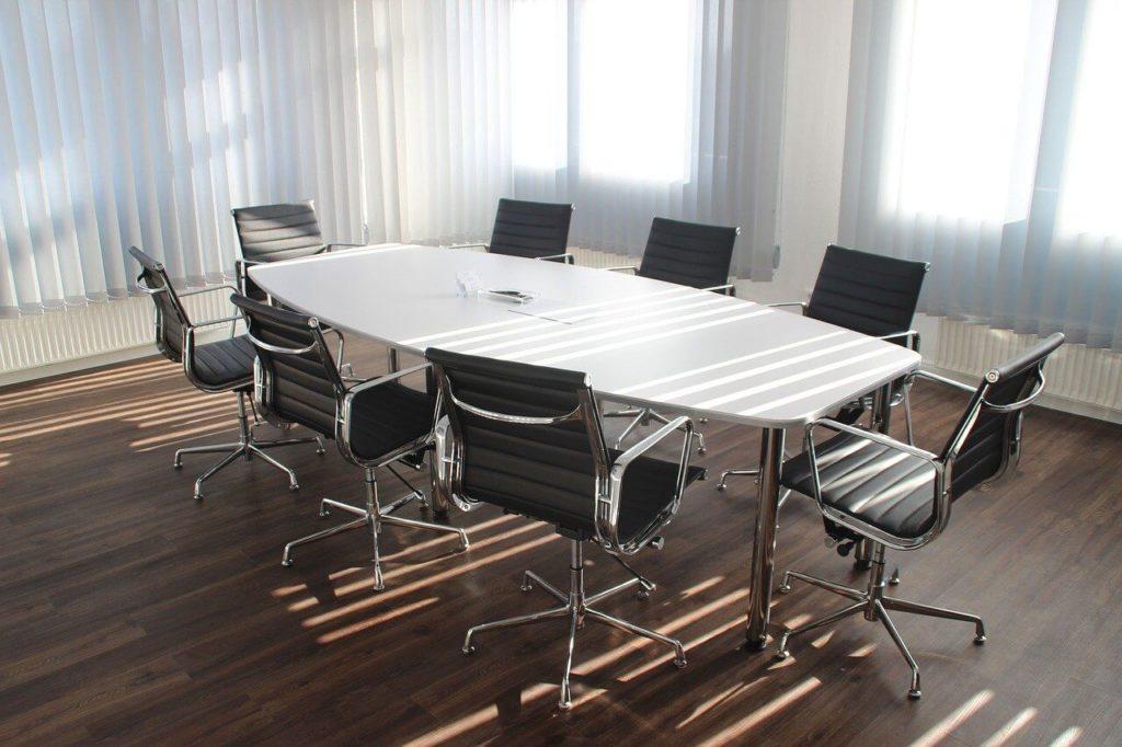 На фото изображен сто и стулья в офисе.