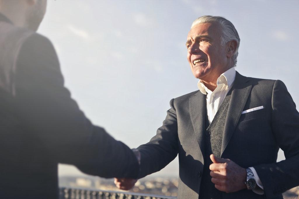 На фото изображено рукопожатие между двумя мужчинами.