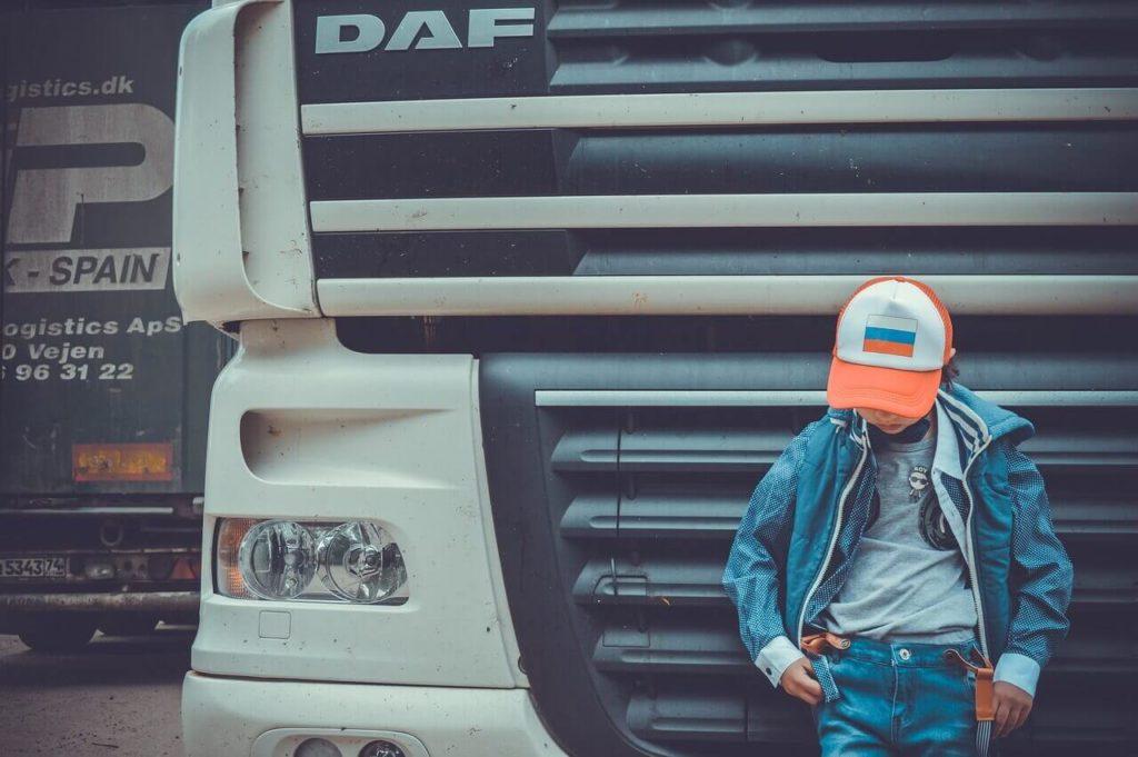 На фото парень стоит возле грузовика.