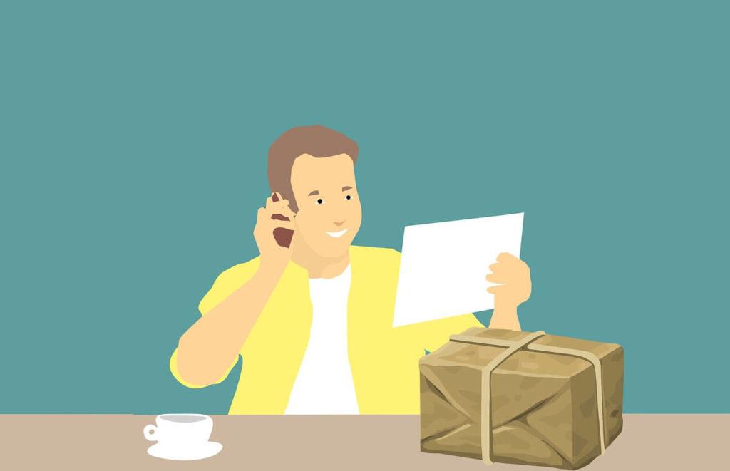 На фото мужчина с посылкой разговаривает по телефону.