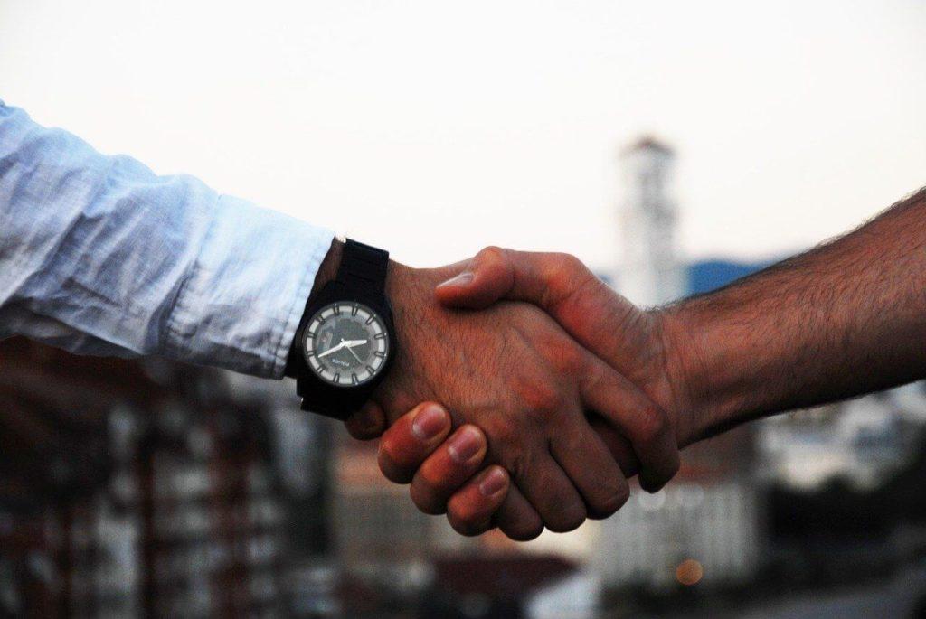На фото изображено рукопожатие мужчин.