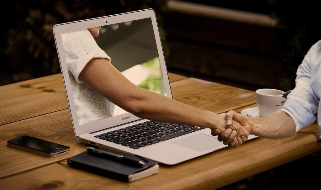 На фото происходит укопожатие через экран ноутбука.