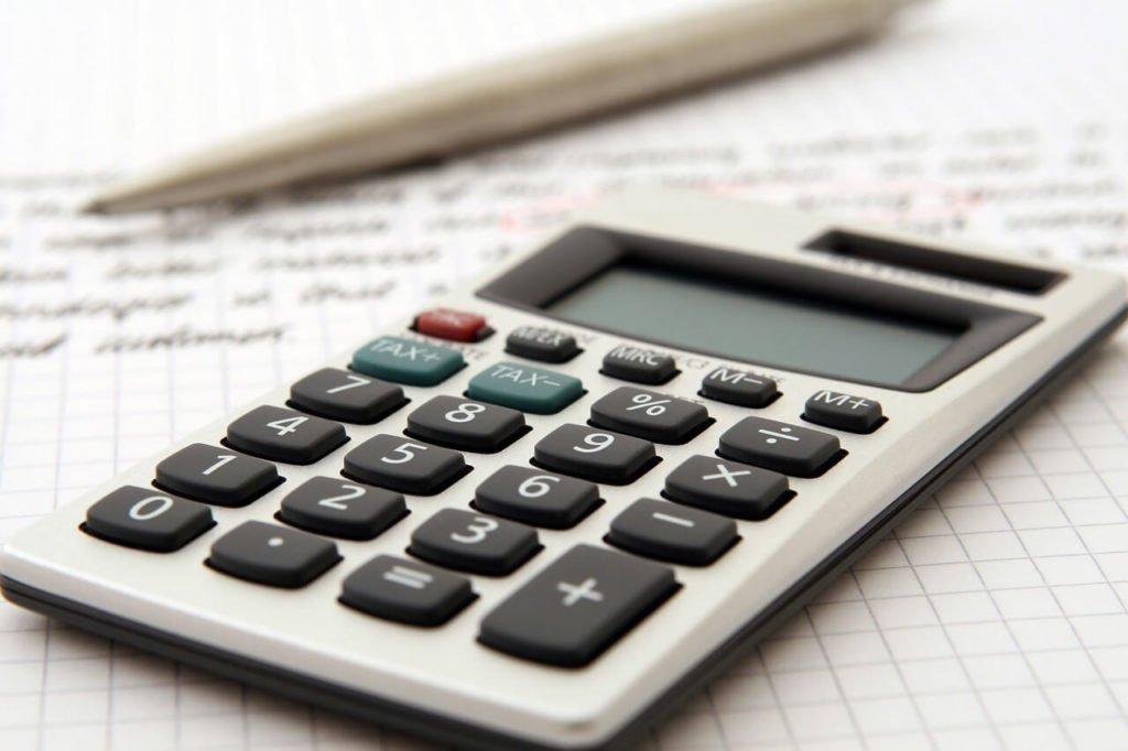 На фото изображен калькулятор, ручка и документ.