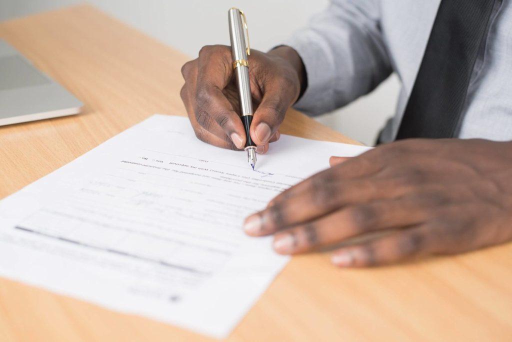 На фото иностранец подписывает документ.