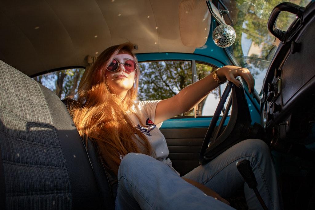 На фото девушка в очках за рулем автомобиля.
