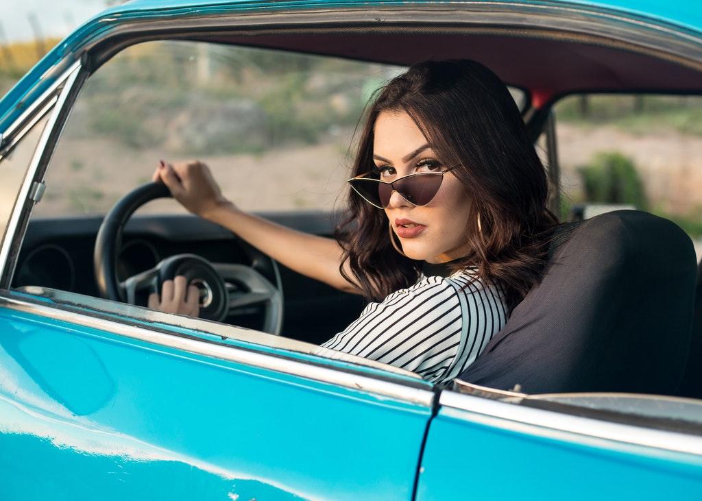 На фото девушка выглядывает из окна авто.