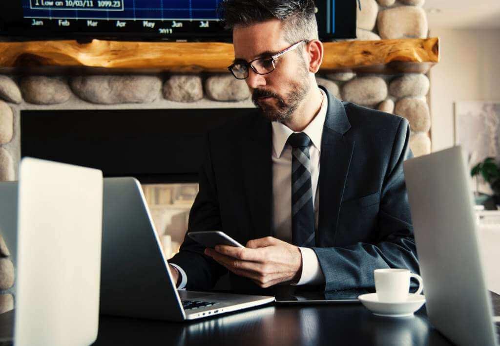 На фото человек с телефоном работает за ноутбуком.