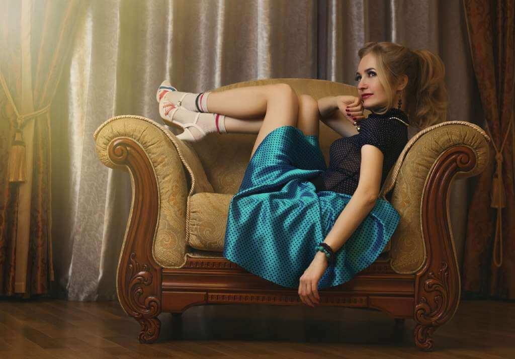 На фото девушка лежит на кресле.