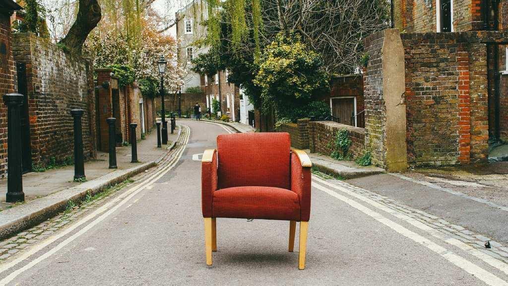 На фото кресло на дороге.