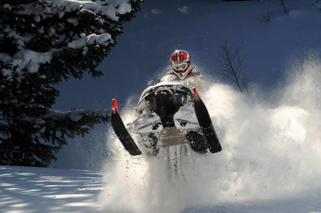 На фото изображен человек на снегоходе.