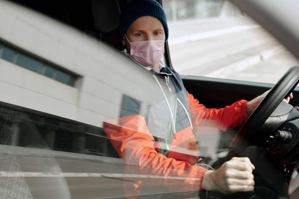 На фото водитель в маске за рулем автомобиля.