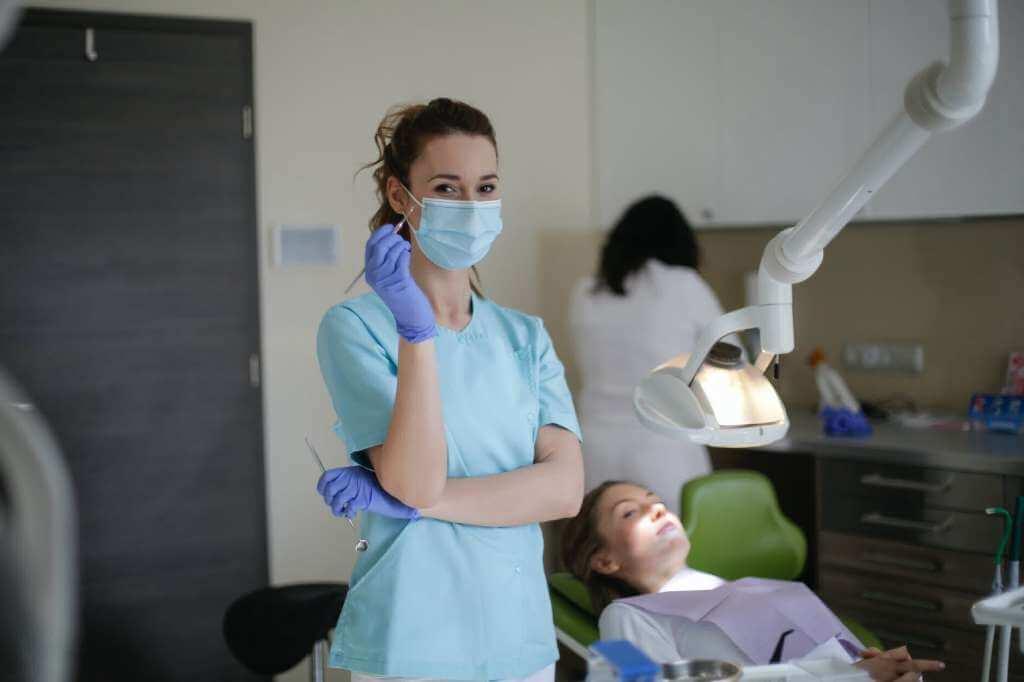 На фото девушка в маске в стоматологическом кабинете.