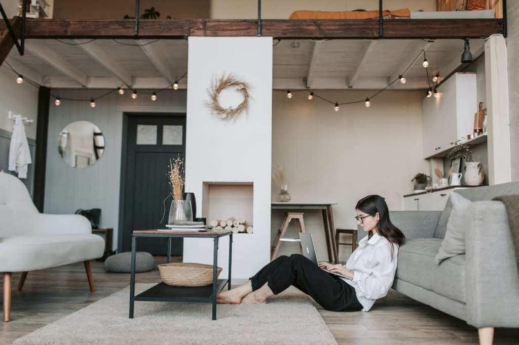 На фото девушка работает в своей квартире.