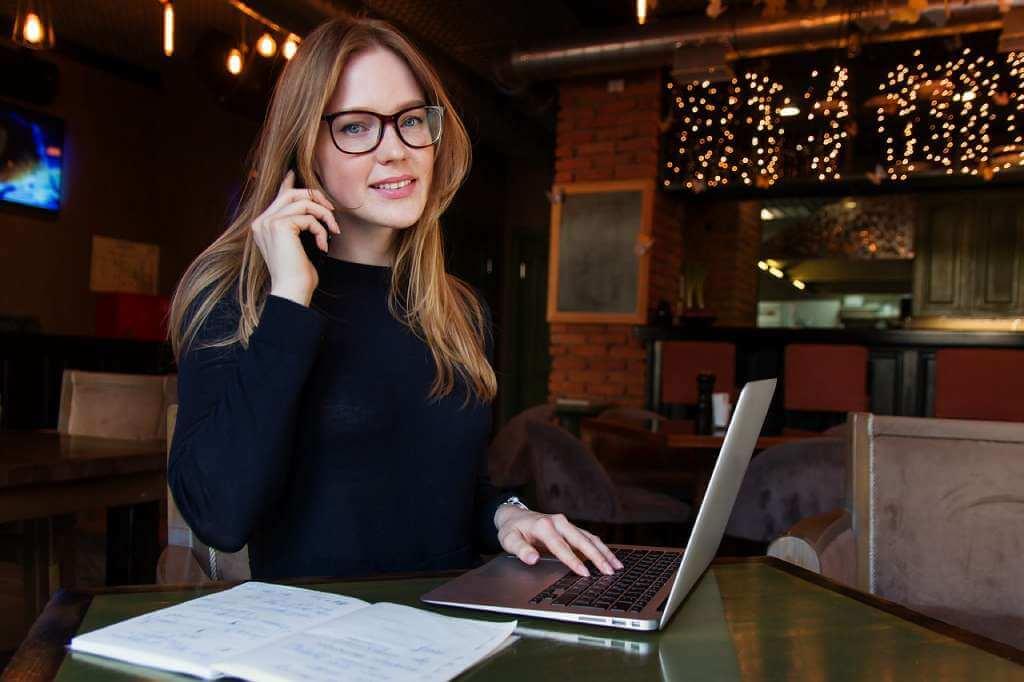 На фото девушка работает за ноутбуком.