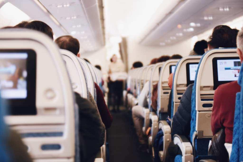 На фото изображены пассажиры в самолете.