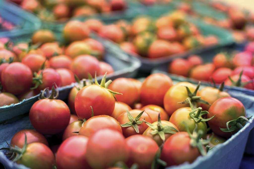 На фото изображены помидоры на прилавке.