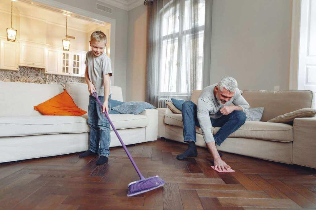 На фото отец с сыном делают уборку в комнате.