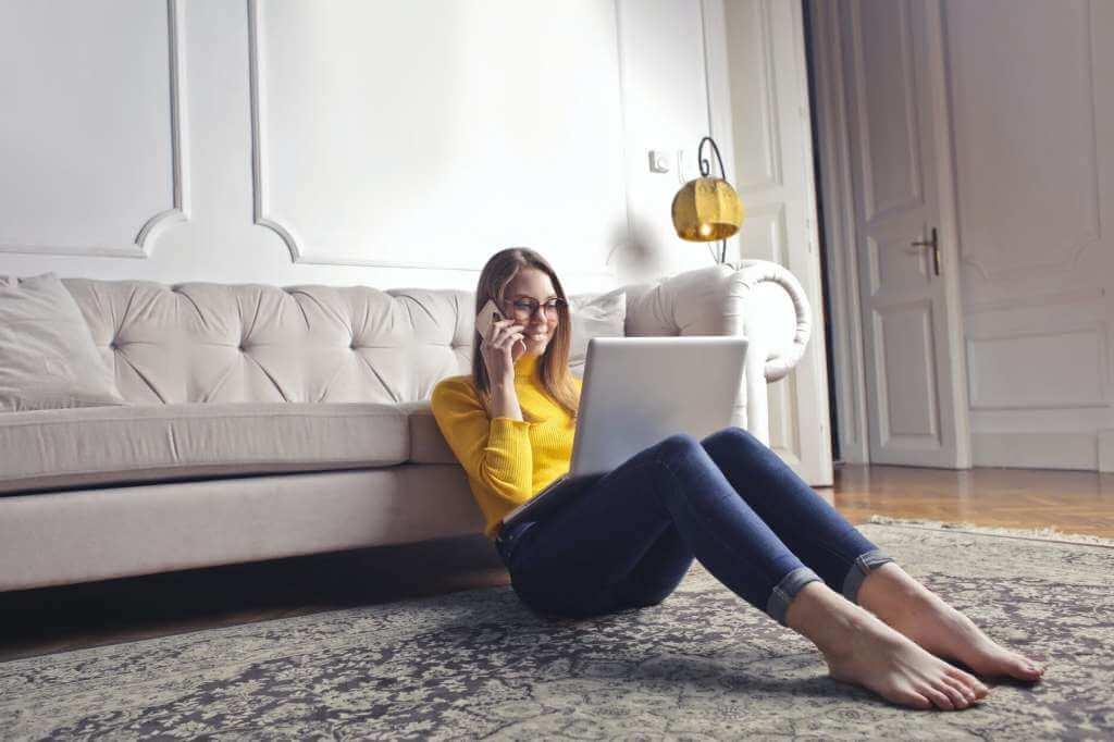На фото девушка сидит на полу с ноутбуком.