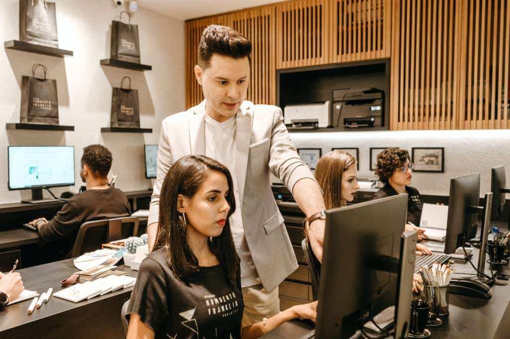 На фото начальник обучает сотрудницу в офисе.